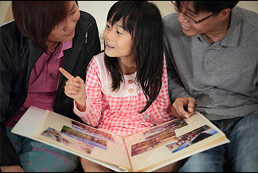 Parents encouraging their child to speak English