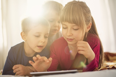 Three children using a tablet to learn English